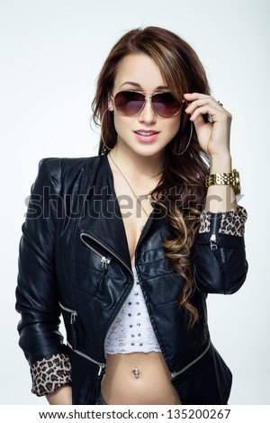 Sexy woman in sunglasses posing on dark background - stock photo