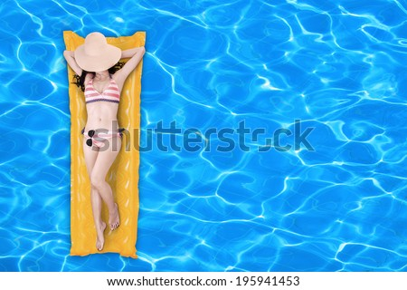 Sexy woman in swimsuit floating on a pool mattress in a swimming pool - stock photo