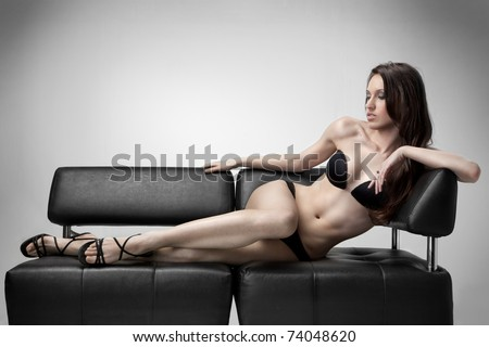 sexy woman in swimsuit lies on the sofa - stock photo