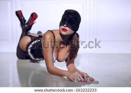 Sexy woman in underwear and lace eye cover kneeling on floor with pearls - stock photo