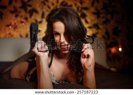 Sexy woman in underwear laying on bed in hotel room, showing handcuffs, seduction - stock photo