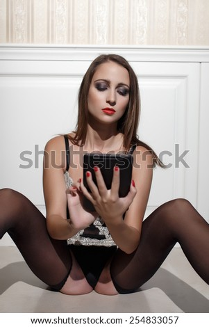 Sexy woman in underwear messaging on tablet at vintage wall - stock photo