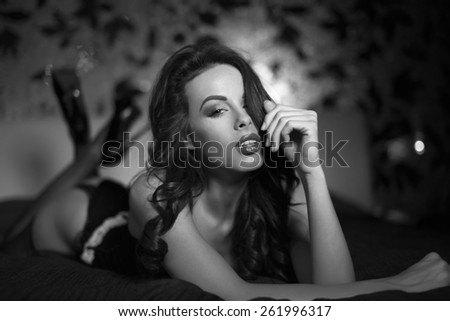 Sexy woman in underwear posing on bed in hotel room, sensual lover, black and white - stock photo