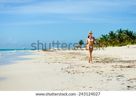 Sexy woman in white bikini enjoying idyllic tropical beach and caribbean summer vacation. Beautiful tanned brunette enjoying a relaxing walk by the sea at Playa Paraiso, Riviera Maya, Mexico. - stock photo
