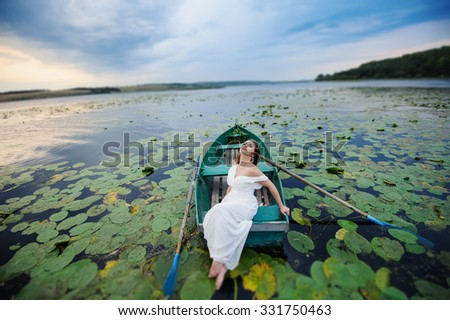 Sexy woman in white dress on the boat - stock photo