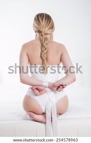 Sexy woman in white panties with hands tied from back - stock photo