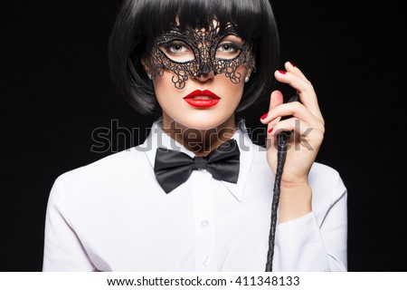 Sexy woman in wig posing with whip on black background, sensuality and punishment - stock photo