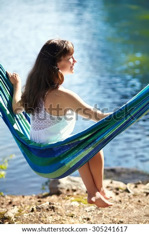 sexy woman is relaxing in a hammock outdoors - stock photo
