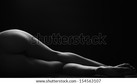 Sexy woman lies, darkness, light contours, wet skin - stock photo