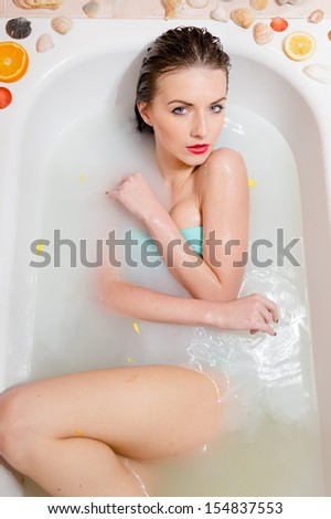 sexy woman looking at camera relaxing in milk bath with flowers - stock photo
