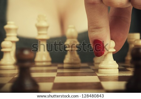 sexy woman playing chess and hold pawn - stock photo