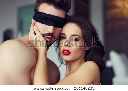 Sexy woman playing with young macho lover at home - stock photo