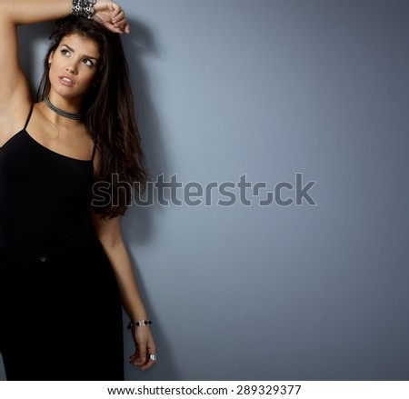 Sexy woman posing by wall, looking away, one hand on top of head. - stock photo