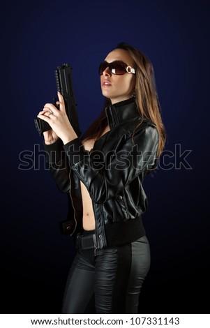 Sexy woman posing with gun in sunglass - stock photo
