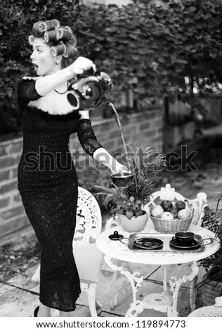 sexy woman pouring tea funny concept - fashion shoot (intentional soft focus and vintage look) - stock photo