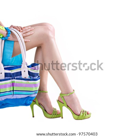 sexy woman's legs in green shoes and handbag isolated on white - stock photo