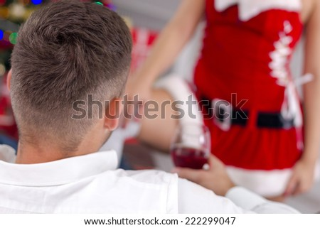 sexy woman santa  in red costume seduces man - stock photo