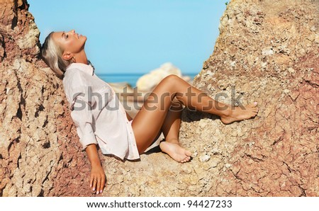 sexy woman sitting at beach enjoying the view of sea - stock photo