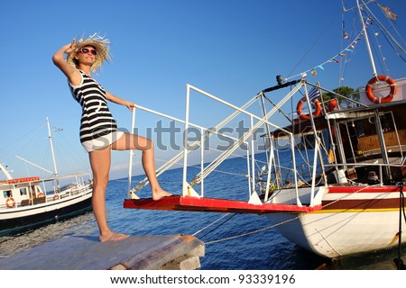 Sexy Woman step on board of Boat - stock photo