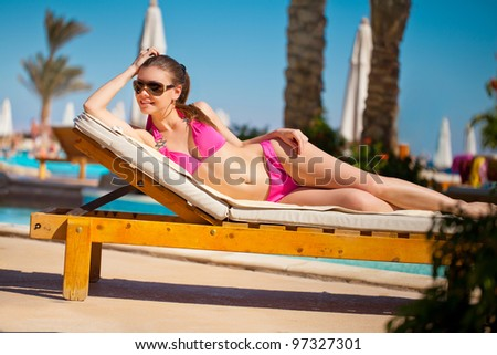 Sexy woman sunbathing on a chaise lounge near pool outdoors - stock photo