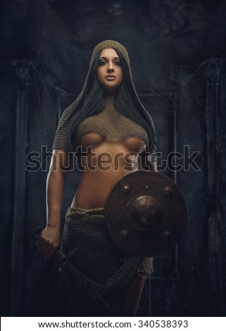 Sexy woman warrior in iron armor holds shield. - stock photo