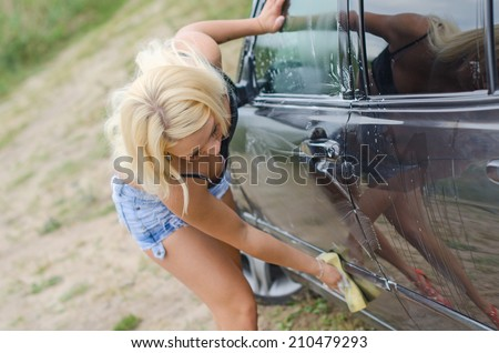 Sexy woman washing car with sponge. - stock photo