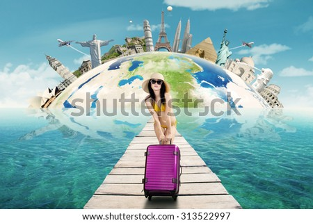 Sexy woman wearing bikini standing on the bridge while holding luggage to travel the worldwide monument - stock photo