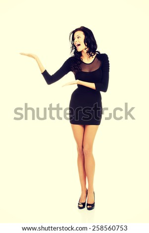 Sexy woman wearing black party dress showing copy space. - stock photo