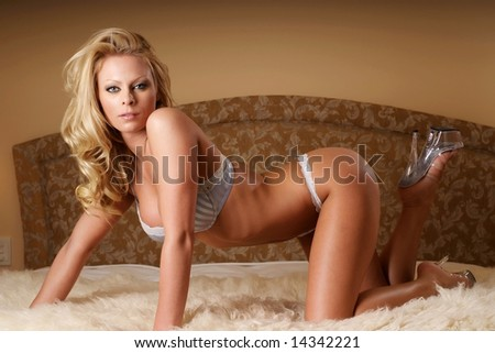 Sexy woman wearing blue lingerie on bed. - stock photo