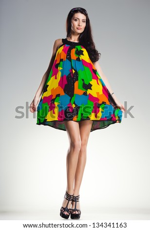 sexy woman wearing colorful summer dress on light grey background - stock photo