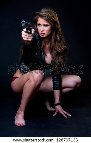 Sexy woman wearing jacket and lingerie holding gun against a black background - stock photo