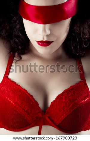 Sexy woman with a red lingerie and blindfolded - stock photo