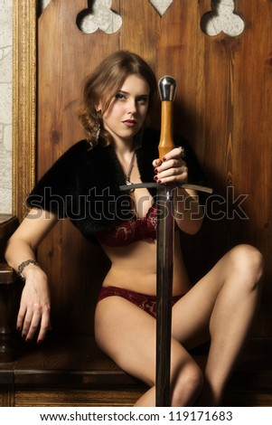 Sexy woman with a sword in a medieval castle interior - stock photo