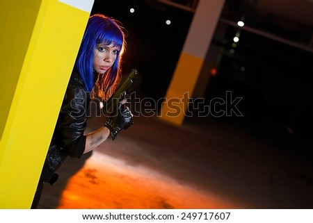Sexy woman with blue hair holding two guns and looking as killer in underground parking - stock photo