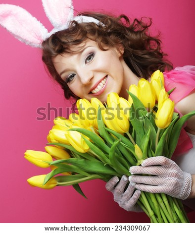 Sexy Woman with Bunny Ears holding yellow tulips - stock photo