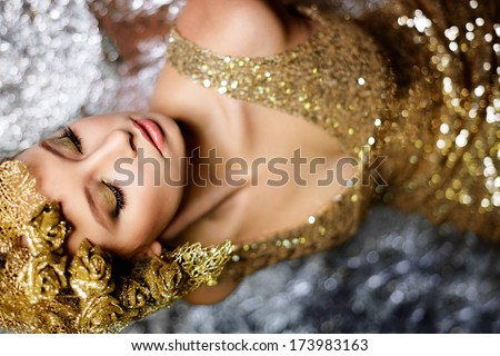 sexy woman with gold roses and leaves in gold dress on silver background - stock photo