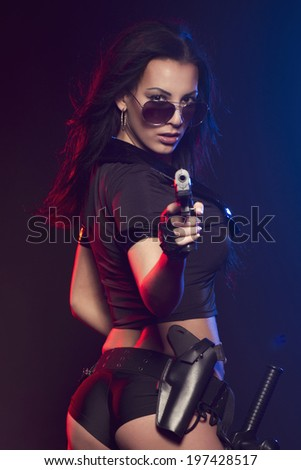 Sexy woman with police uniform in studio on dark red and blue background  - stock photo