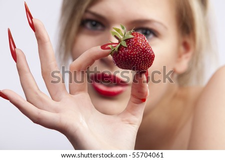 Sexy women with long red nails holding single strawberry - stock photo