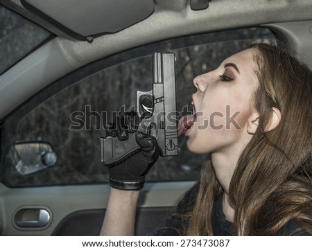 Sexy young adult Girl licking gun inside modern car in dusk evening light Vampire woman pistol in hand Killer female - stock photo