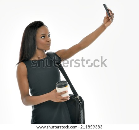 "Sexy young African-American business woman in black dress - studio shot - holding coffee with briefcase over shoulder and taking a ""selfie"" with mobile phone - stock photo"
