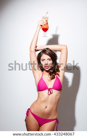 Sexy young beautiful brunette girl holding summer cocktail and posing isolated on the white background - stock photo