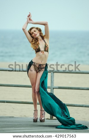 Sexy young beautiful woman in bikini and fluttering cover up posing on the boardwalk at the beach. - stock photo