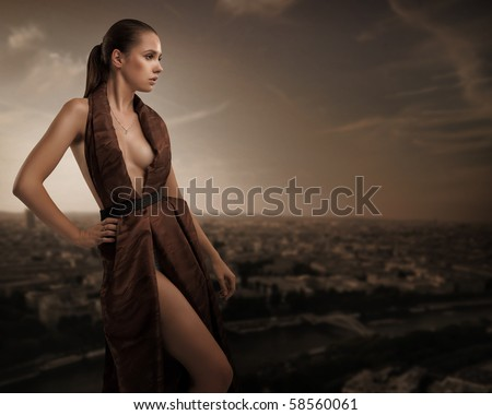 Sexy young beauty posing over urban background - stock photo