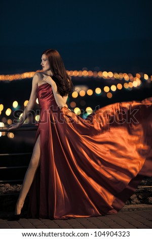Sexy young beauty woman in fluttering red dress - stock photo