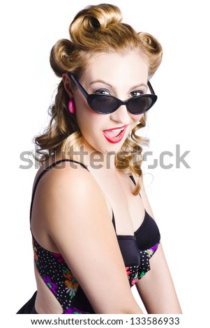Sexy young blond haired woman in swimsuit looking over top of sunglasses, white background - stock photo