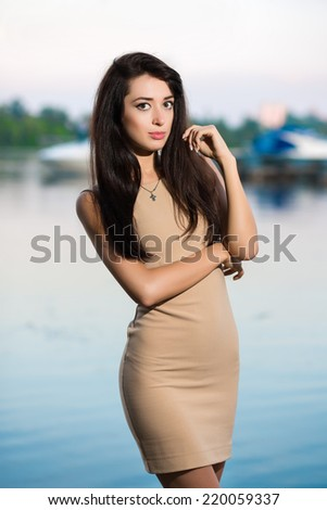 Sexy young brunette posing beige dress outdoors - stock photo