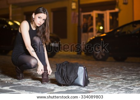 Sexy young brunette wearing black dress sitting near the road - stock photo