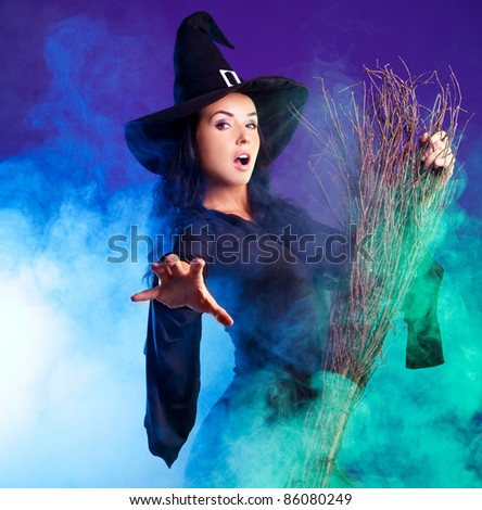 sexy young brunette witch with a broom stretching her hand to us, against purple background - stock photo