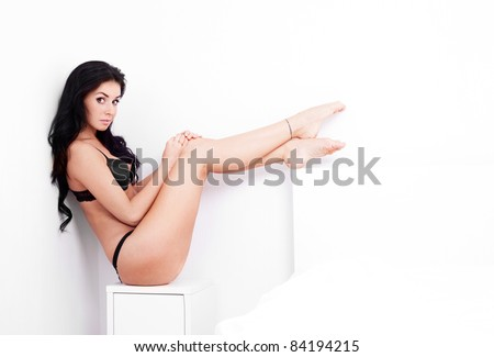sexy young brunette woman wearing underwear in her bedroom at home - stock photo