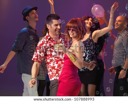 sexy, young couple flirting on the dancefloor in a night club - stock photo